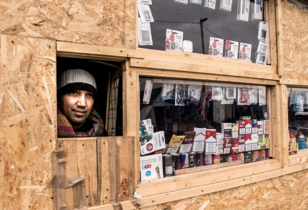 "A Pakistani migrant looks out of his shop set-up at ""the Jungle"" in the French port city of Calais."