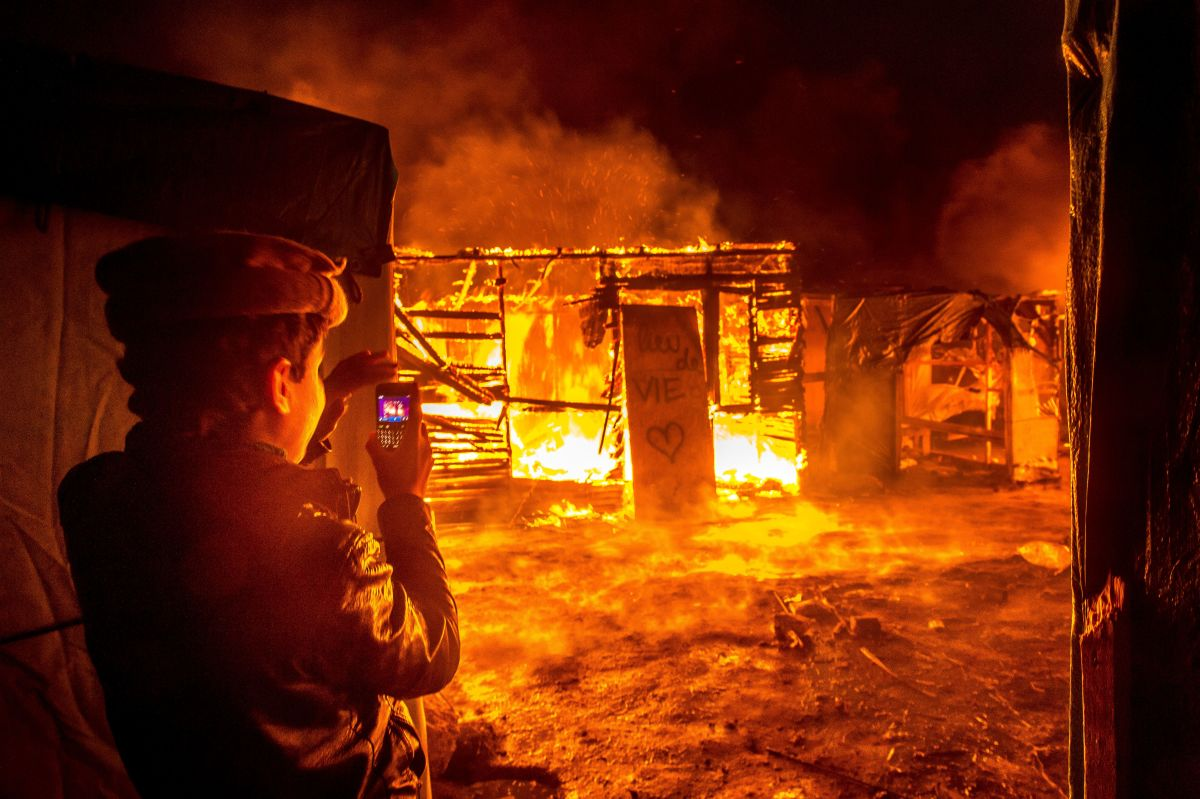 """A young Afghan migrant films with his phone a fire burning shacks and a placard reading """"living space"""" in the southern part of """"the Jungle"""" migrant camp."""