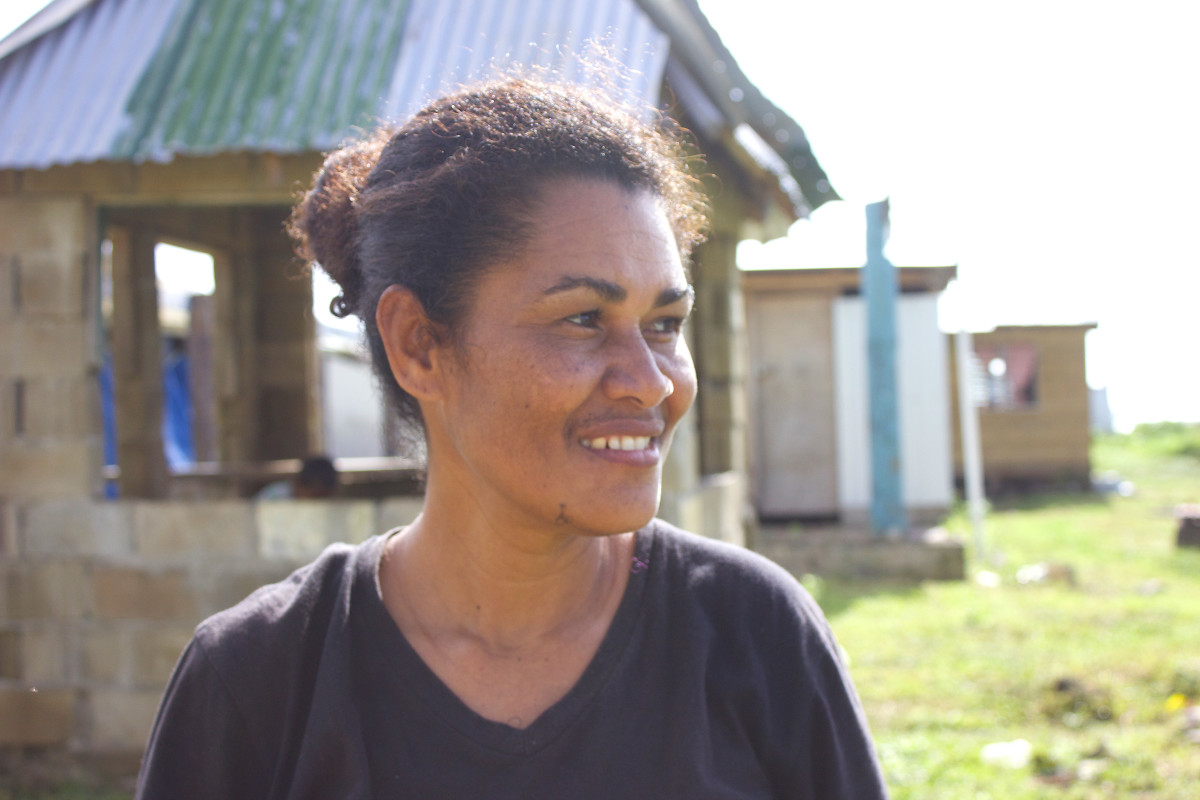 In Nasau, on Koro island, La Venia stands in front of houses that are still being rebuilt.