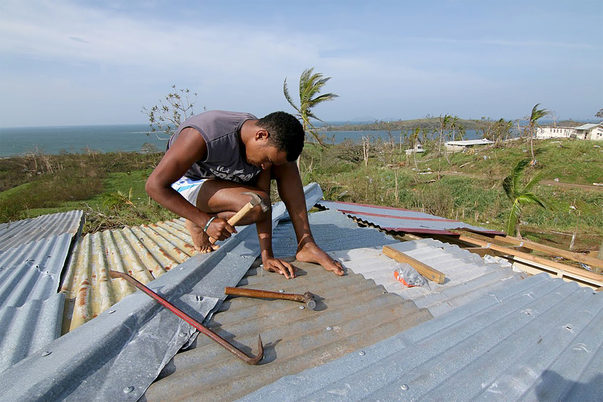A young man repairs the roof of his house in Tailevu after Cyclone Winston swept through Fiji in 2016.