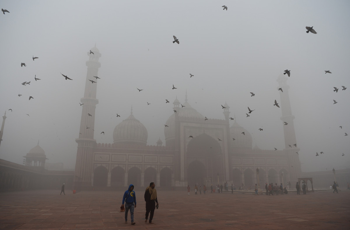 Indian visitors walk through the courtyard of the Jama Masjid mosque amid heavy smog in the old quarters of New Delhi on November 8th, 2017. The city's pollution levels hit nearly 30 times the World Health Organization safe level on Wednesday.