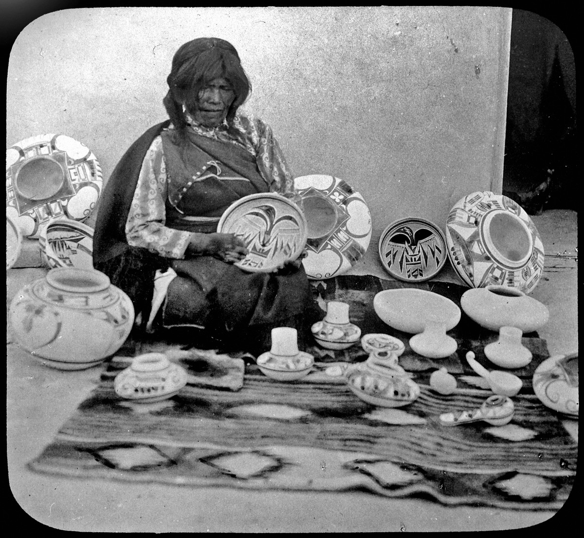 Nampeyo, a Hopi pottery maker seated with examples of her work.