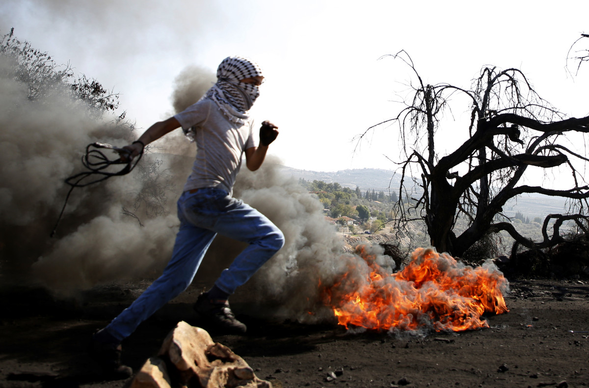 A Palestinian protester runs past burning tires during a clash with Israeli forces over occupation in the village of Kfar Qaddum, near the occupied West Bank, on November 10th, 2017.