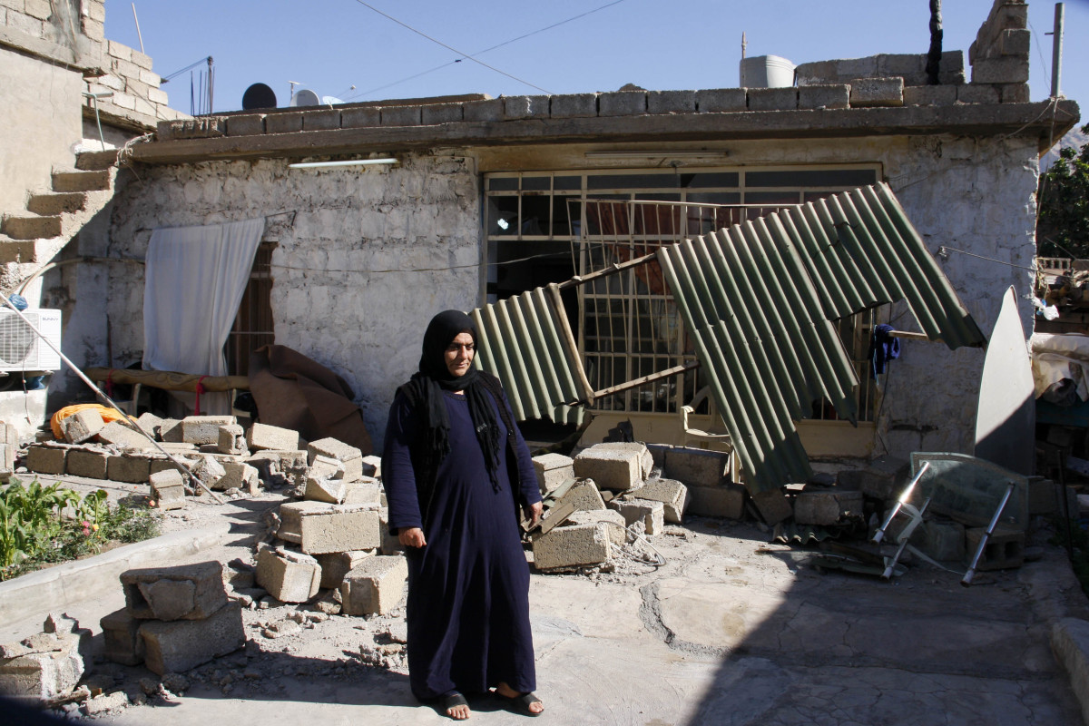 A woman stands in the yard next to her damaged home in the mountainous town of Darbandikhan in Iraqi Kurdistan on November 13th, 2017.
