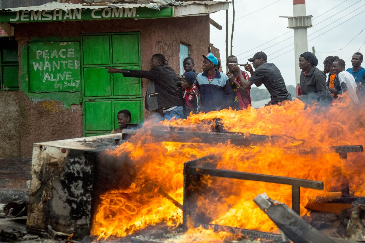 Supporters of Kenya's opposition party take shelter during a demonstration in Nairobi on November 20th, 2017, after Kenya's supreme court dismissed petitions to overturn the country's presidential election re-run, validating the poll victory of President Uhuru Kenyatta.