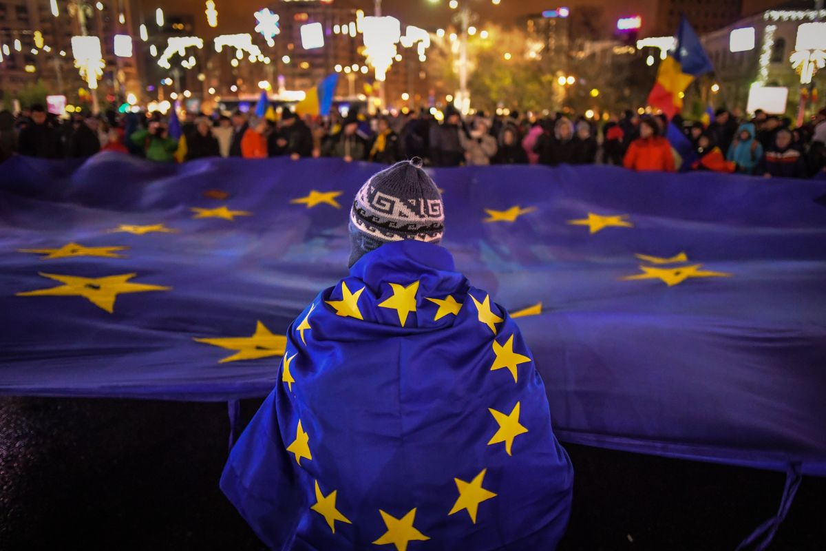 Protesters hold a European Union flag during an anti-government and corruption protest at the Victoria square in front of the Romanian government headquarters, in Bucharest, on December 3rd, 2017.