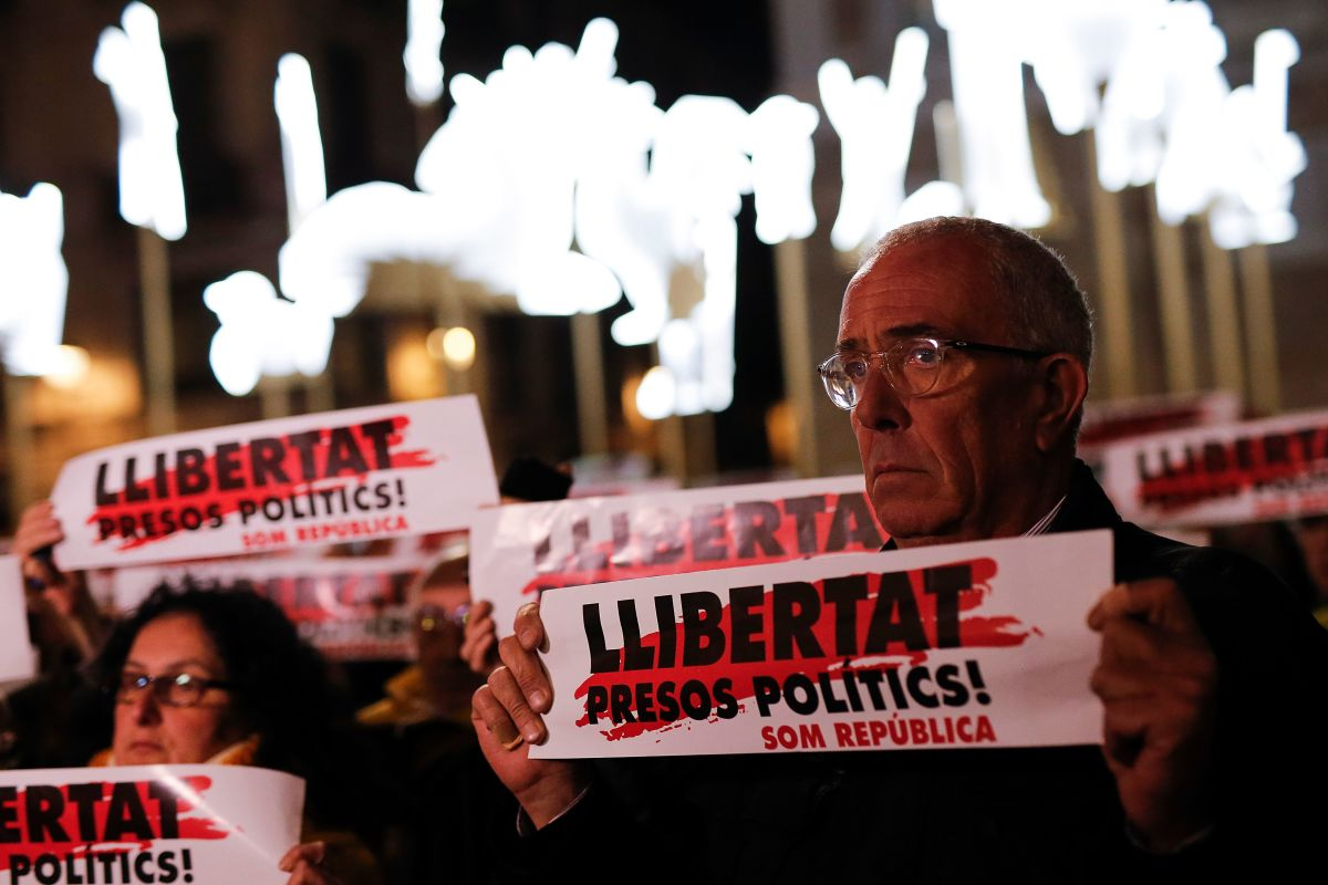 People hold banners reading Freedom for Political Prisoners in front of Barcelona's city hall on December 4th, 2017, during a demonstration demanding the release of jailed separatist leaders.