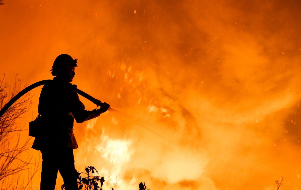 A firefighter battles a wildfire as it burns along a hillside near homes in Santa Paula, California, on December 5th, 2017.