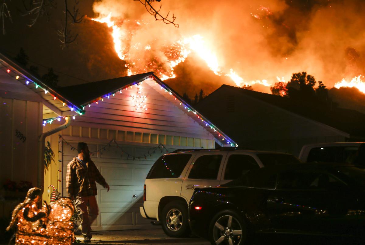 A man prepares to evacuate his home as a wildfire burns along a hillside near homes in Santa Paula, California.