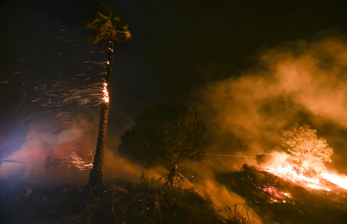 A firefighter battles a wildfire as it burns along a hillside near homes in Santa Paula, California.