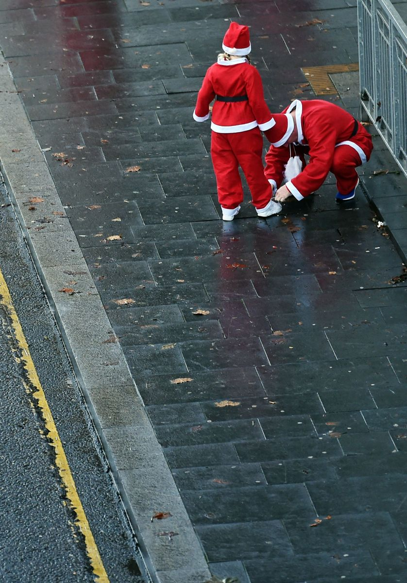 Runners dressed in Father Christmas costumes arrive to take part in the annual five kilometer Santa Dash in Liverpool, England, on December 3rd, 2017. Many runners wear a blue suit, usually the supporters of Everton football club, rather than a red one, as red is the color of their bitter rivals, the Liverpool football club.