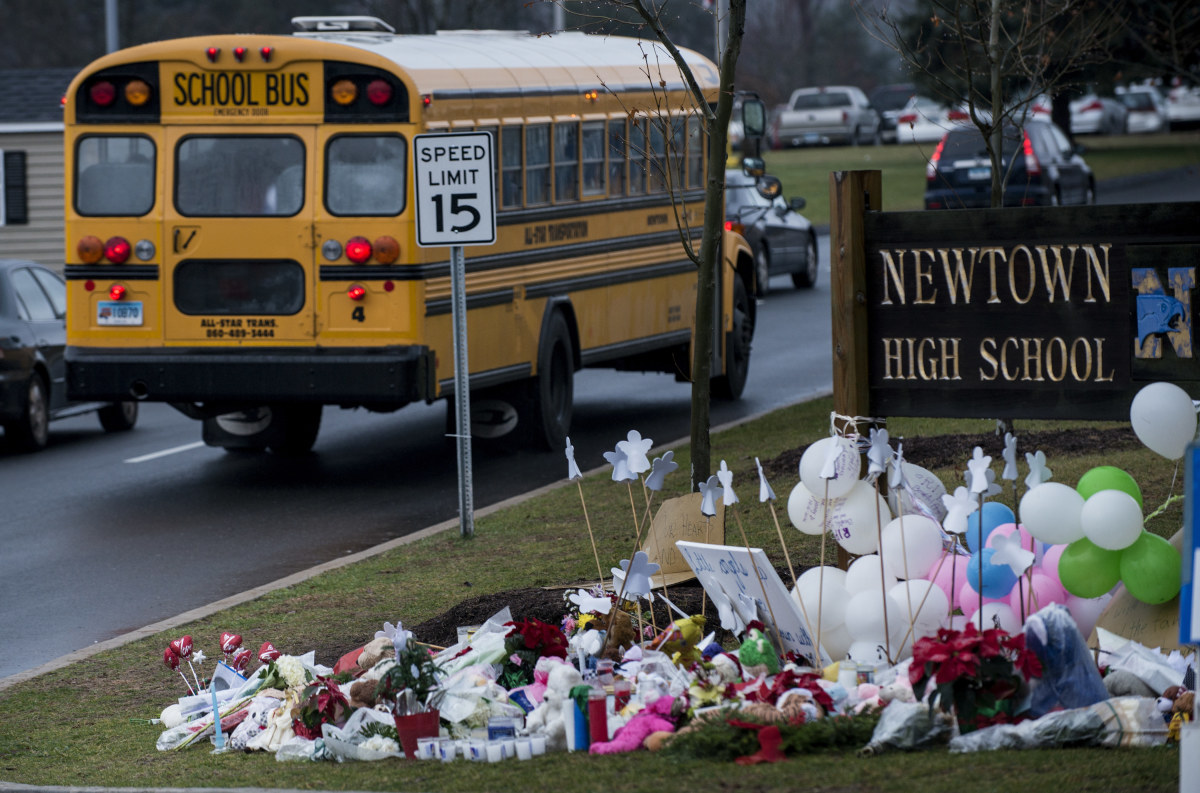 A school bus passes a memorial to the victims of the Sandy Hook Elementary School shooting in Newtown, Connecticut, on December 18th, 2012.