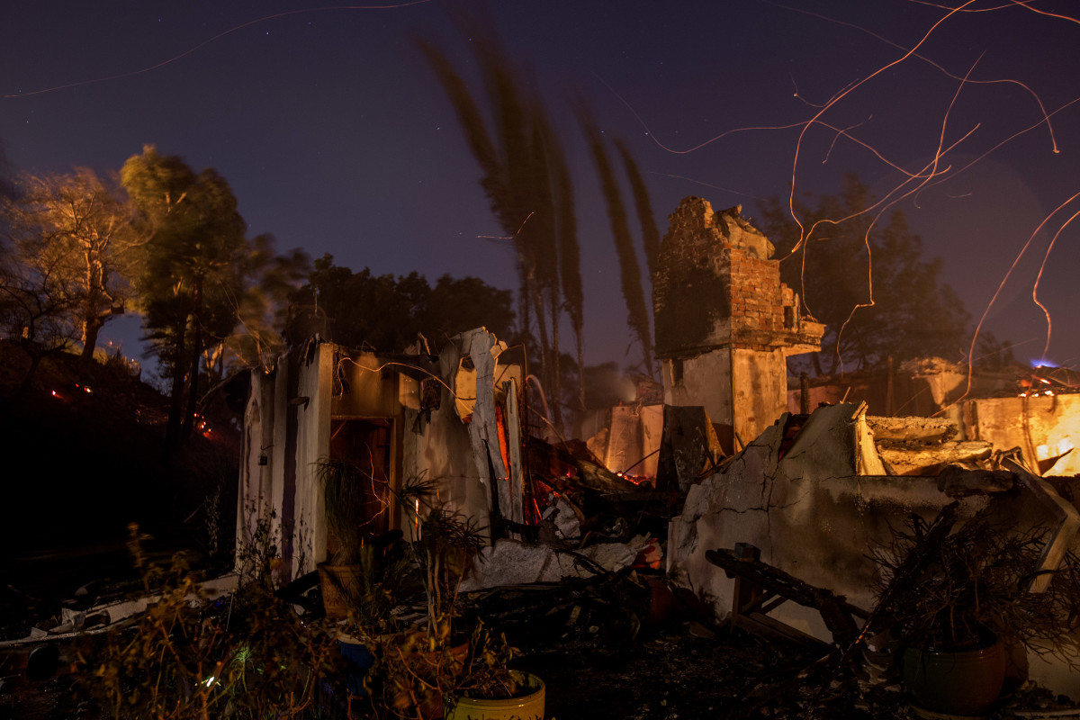 Strong wind blows embers across the smoldering ruins of a house at the Creek Fire in Sunland, California. Strong Santa Ana winds are rapidly pushing multiple wildfires across the region, expanding across tens of thousands of acres and destroying hundreds of homes and structures.