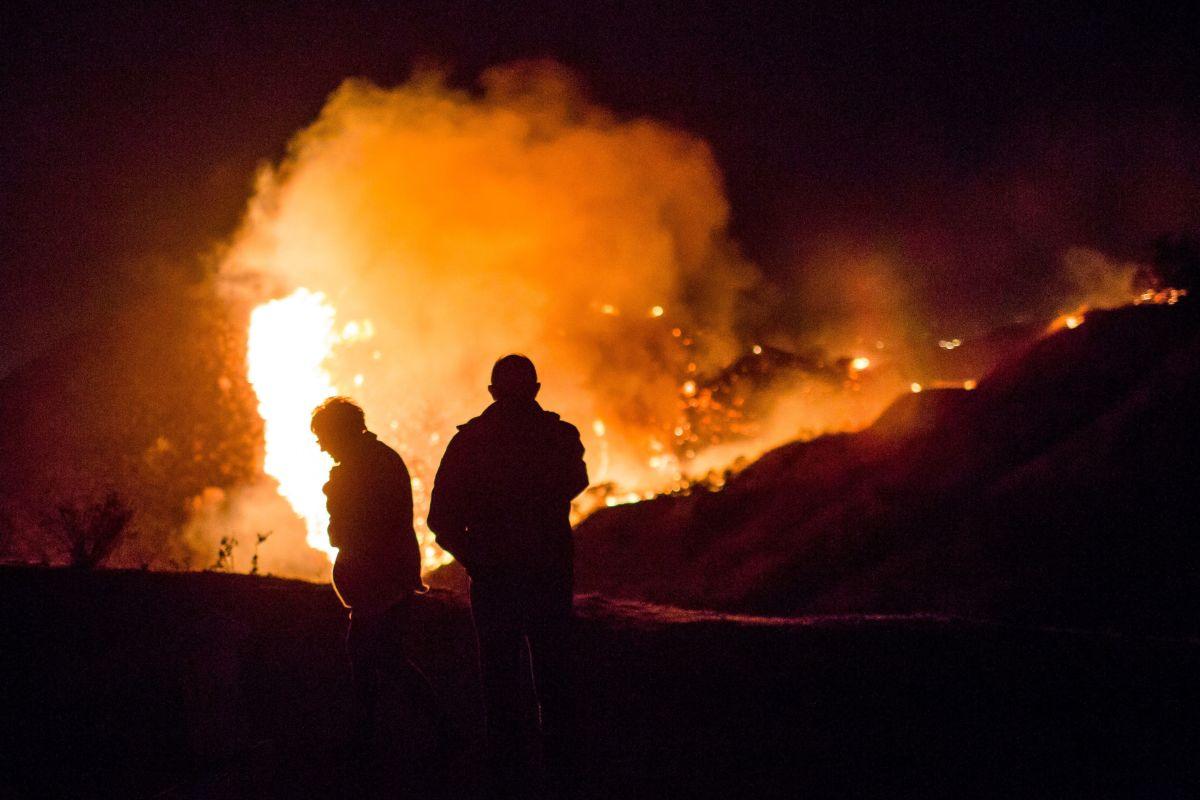 Spectators watch as the Creek Fire burns along a hillside near homes in the Shadow Hills neighborhood of Los Angeles, California.