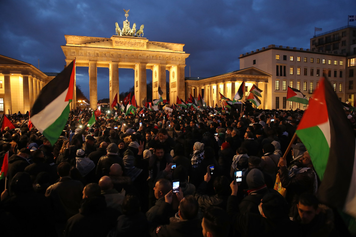People waving Palestinian and Turkish flags gather in front of the Brandenburg Gate to protest against U.S. President Donald Trump's announcement to recognize Jerusalem as the capital of Israel on December 8th, 2017, in Berlin, Germany.
