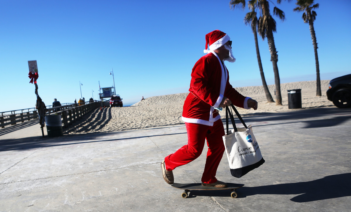 Jake Glaser, dressed as Santa Claus, skateboards at Venice Beach on December 13th, 2017, in Los Angeles, California. Residents are preparing for Christmas in the wake of a series of destructive wildfires across Southern California.