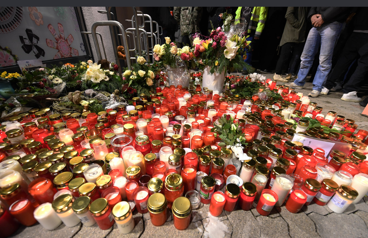 Candles and flowers are displayed outside a grocery store on January 2nd, 2018, where a 15-year-old girl was stabbed to death by her ex-boyfriend in the western German town of Kandel.