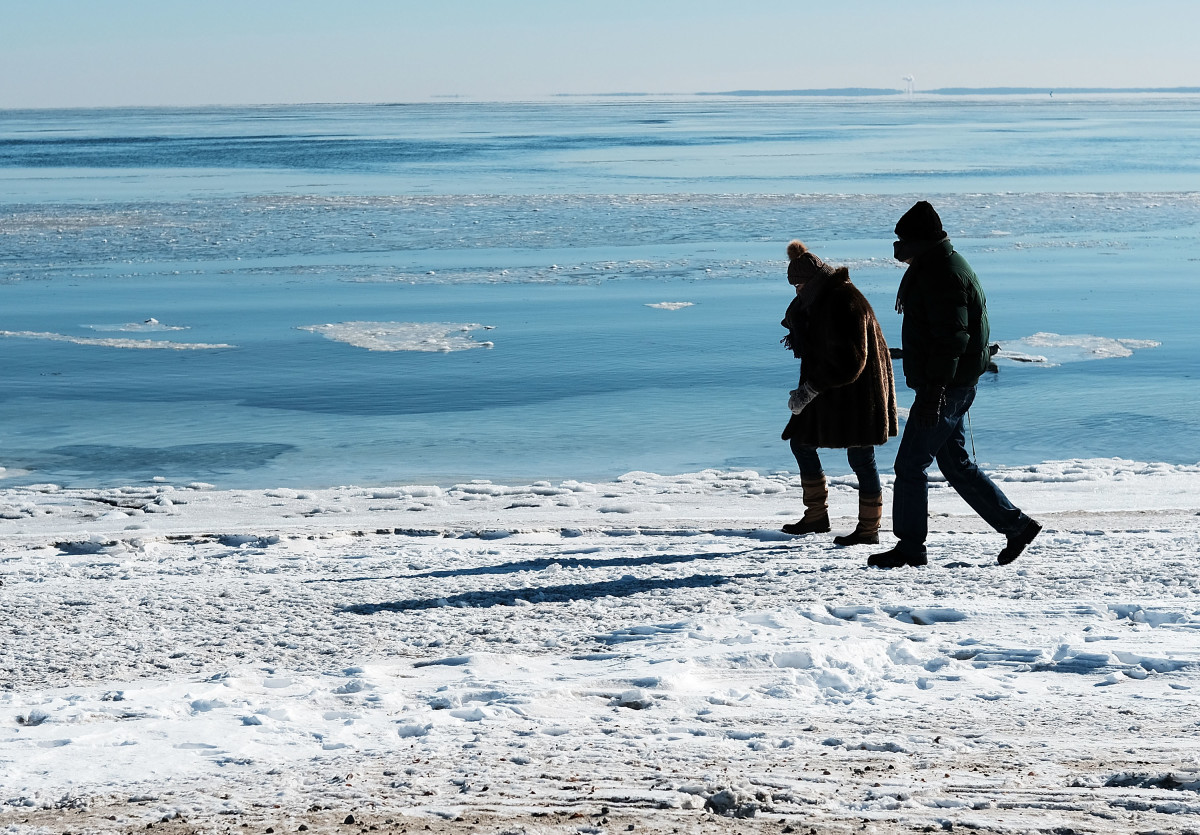 People walk along a beach covered in snow and ice in Westport, Connecticut, on January 7th, 2018. Following a heavy snowfall last week, much of New England is experiencing Arctic-like weather conditions.