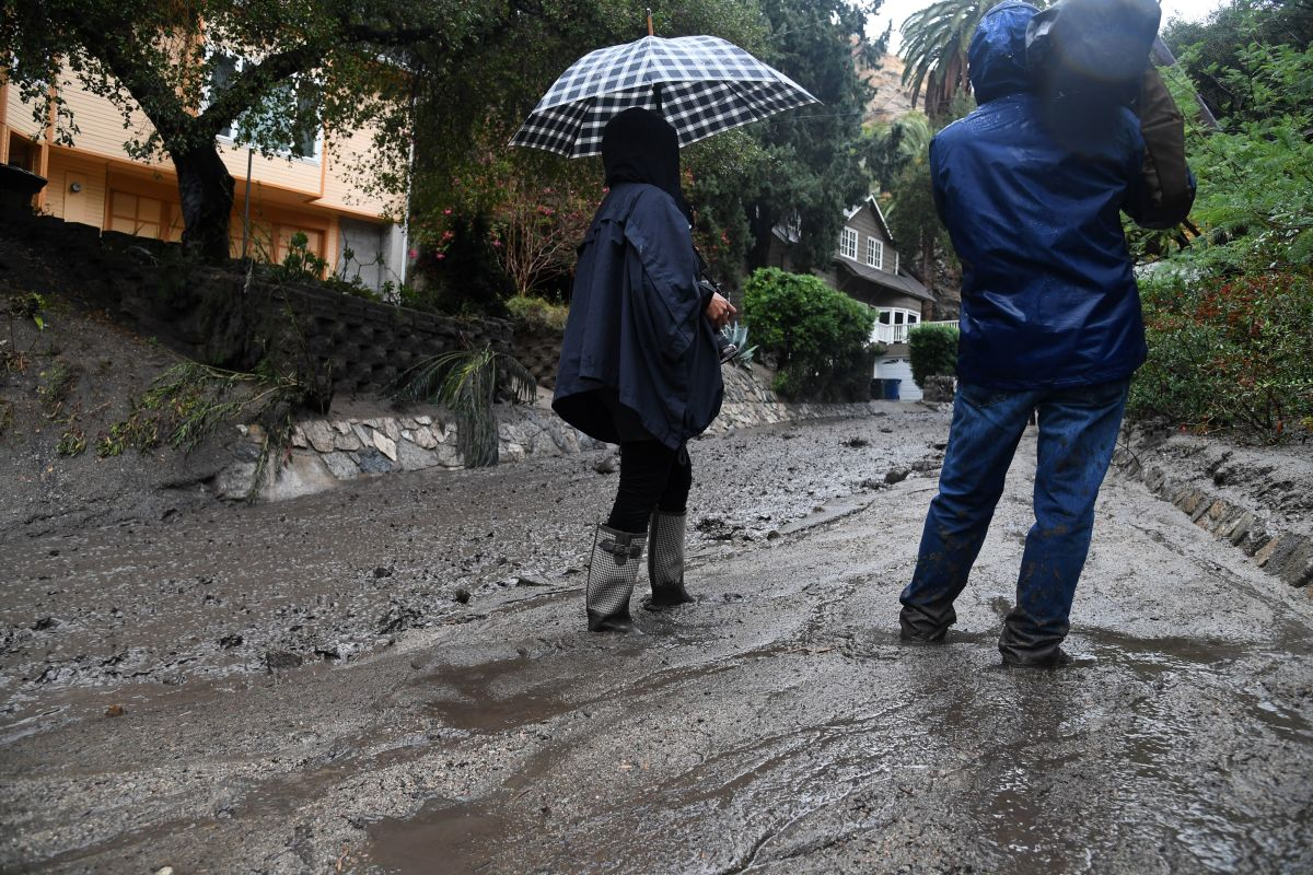 Journalists stand in ankle-deep mud in Burbank, California, on January 9th, 2018.