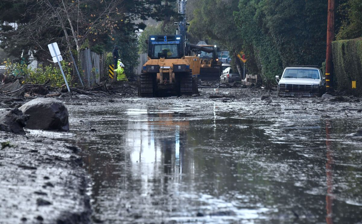 A car remains stuck as a clean-up crew works to clear mud beside a closed-off section of the 101 Freeway in Montecito, California, on January 9th, 2018.