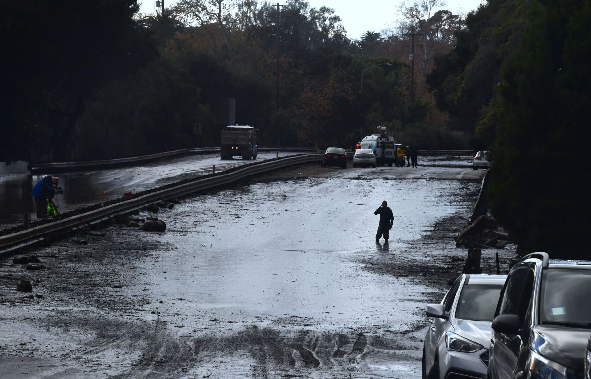 A man wades through a flooded section of the 101 Freeway in Montecito, California, on January 9th, 2018.