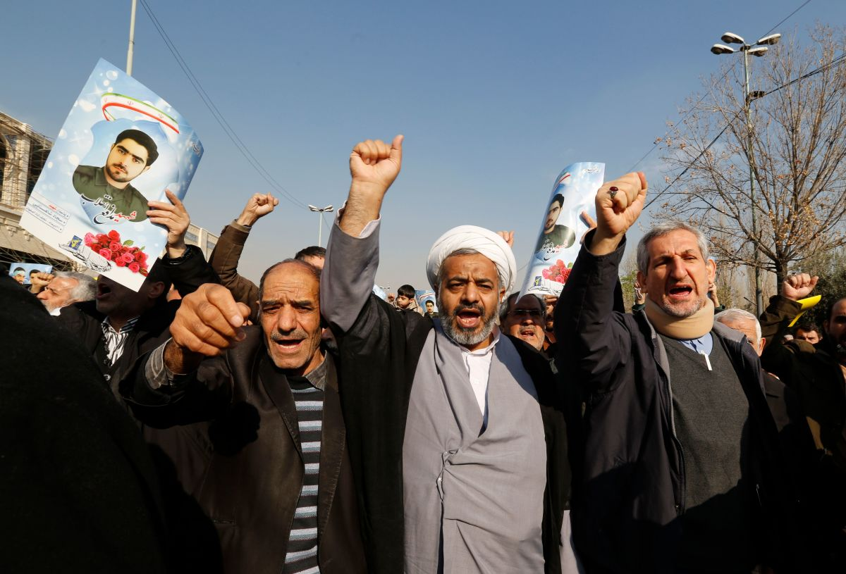Iranian pro-government protesters, holding up portraits of Sajjad Shahsanai, a young member of the Revolutionary Guards killed in unrest in the city of Najafabad, shout slogans during a march after the weekly Friday prayers in Tehran on January 5th, 2018.