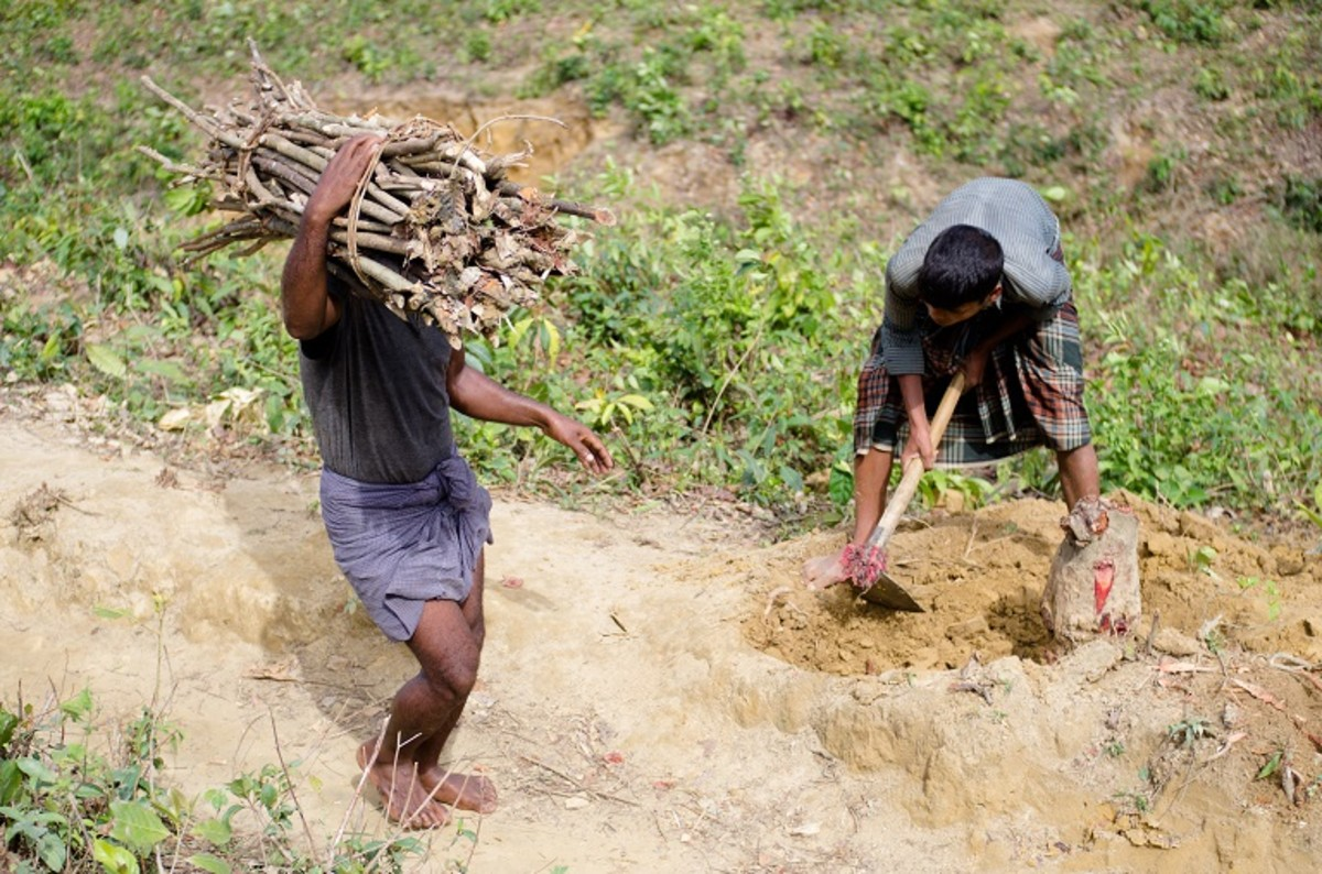 A Rohingya boy chopping wood from a tree stump he freed from soil near Kutupalong-Balukhali refugee camp in Bangladesh.
