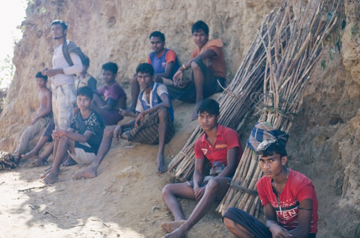 A group of Rohingya men take a break on the long route home from collecting firewood from Bangladeshi forests.