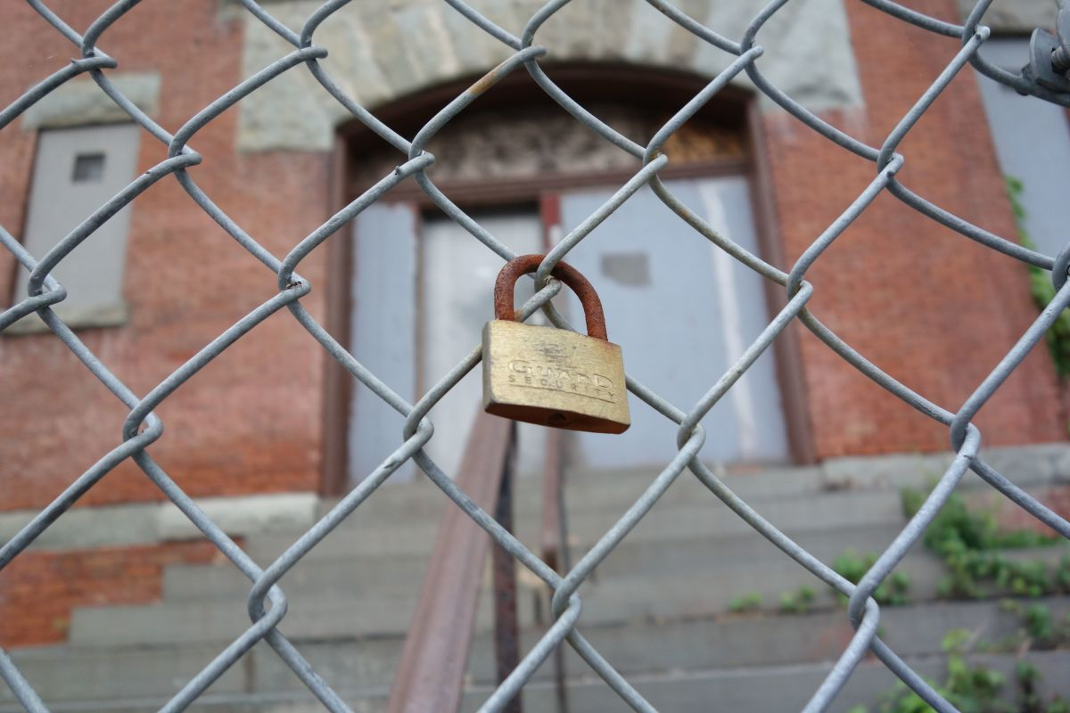 A padlock hangs outside a shuttered schoolhouse in New York.