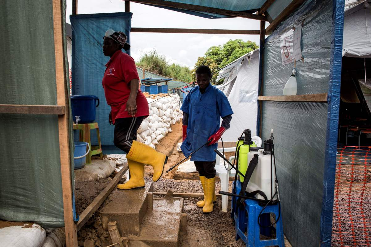 A worker at an emergency cholera treatment center gets her shoes disinfected in Kinshasa, the Democratic Republic of the Congo, on January 18th, 2018. The World Health Organization said this week that there was a high risk of a cholera epidemic after flooding in the area.