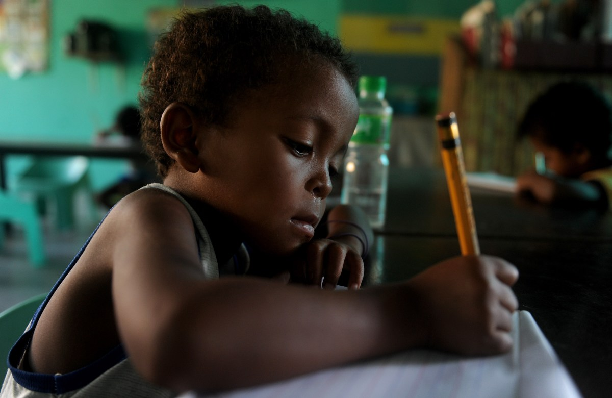 Agta children write as they attend school in Sapang Uwak, in the Philippines.