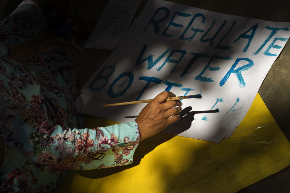 A woman writes on a placard on January 28th, 2018, prior to a protest in Cape Town, South Africa, against the means by which the city council has dealt with water shortages.