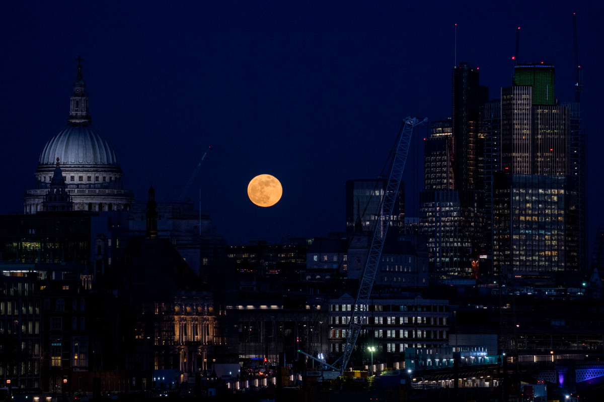 A supermoon rises behind St. Paul's Cathedral and skyscrapers on January 31st, 2018, in London, United Kingdom. The Super Blue Blood Moon is a rare simultaneous combination of a supermoon, a blood moon, and a blue moon.
