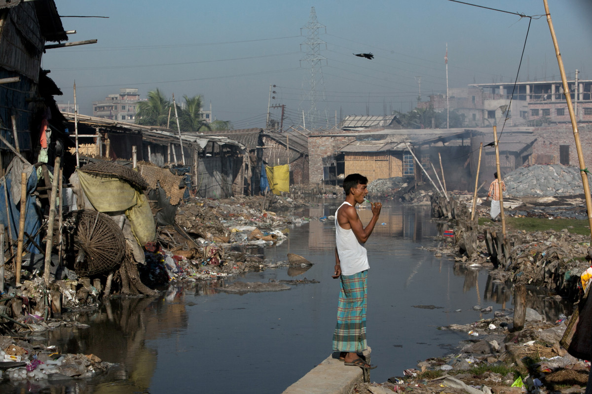 Dhaka, Bangladesh: Momin Mohammad, a leather worker, brushes his teeth by a canal near his home in the city's polluted Hazaribagh neighborhood. Each day, tanneries dump 22,000 liters of toxic waste into the Buriganga, the capital city's main river and key water supply.