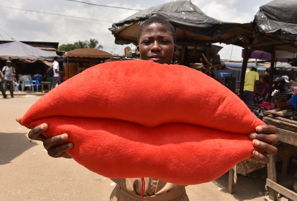 A boy poses with a pillow shaped like lips on sale for Valentine's Day in Yopougon, Ivory Coast, on February 13th, 2018.