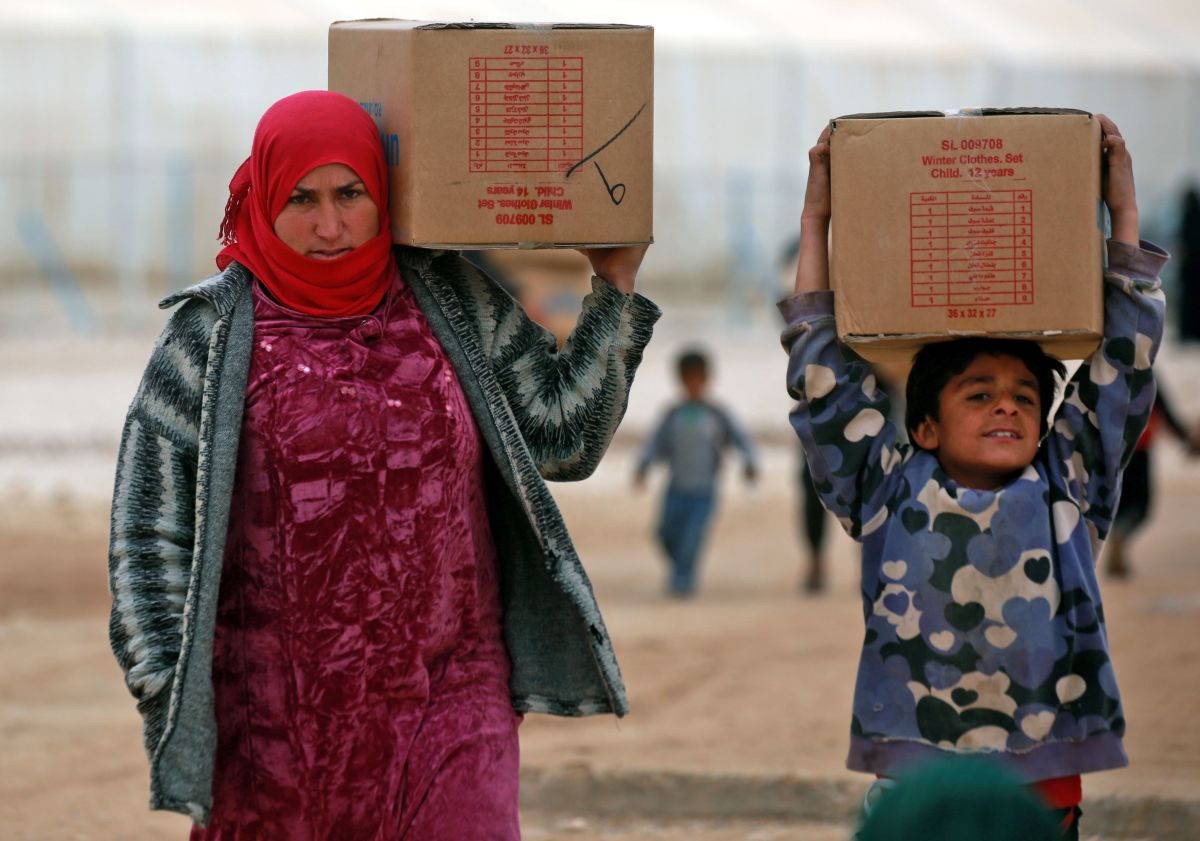 Displaced Syrians, who fled their homes in the eastern Syrian city of Deir Ezzor, carry boxes of humanitarian aid supplied by the United Nations Children's Fund at a refugee camp in Syria's northeastern Hassakeh province on February 26th, 2018.