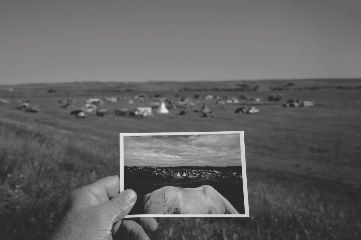 Sacred Stone Village (in the background) was founded by LaDonna Bravebull Allard to carry the vision and energy of the Standing Rock camps forward through teaching young people about Native American history, culture, language, and ways of life. Larry Towell took the photograph of Oceti camp (in the foreground) in September of 2016 during the height of the controversy over the Dakota Access Pipeline. He returned one year later to witness a healing gathering at Sacred Stone Village and to document where the movement is headed.