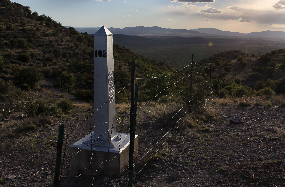 An obelisk and a barbed wire fence mark the U.S.-Mexico border near the Coronado National Memorial in Arizona.