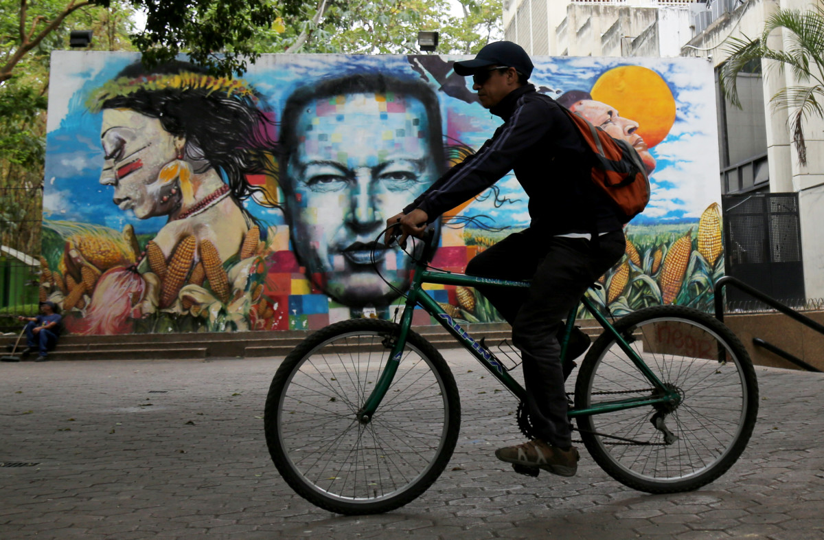 A Venezuelan rides his bike to work in front of a mural of the late President Hugo Chávez near Teresa Carreno Theatre on May 8th, 2019, in Caracas, Venezuela. As the country goes through a political, economic, and social crisis, Venezuelan opposition led by Juan Guaidó, recognized by many more than 50 nations as the country's rightful interim ruler, is still trying to oust Nicolás Maduro after a failed uprising attempt on April 30th.