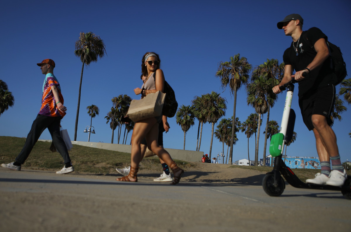 A man rides a shared dockless electric scooter along Venice Beach on August 13th, 2018, in Los Angeles, California.
