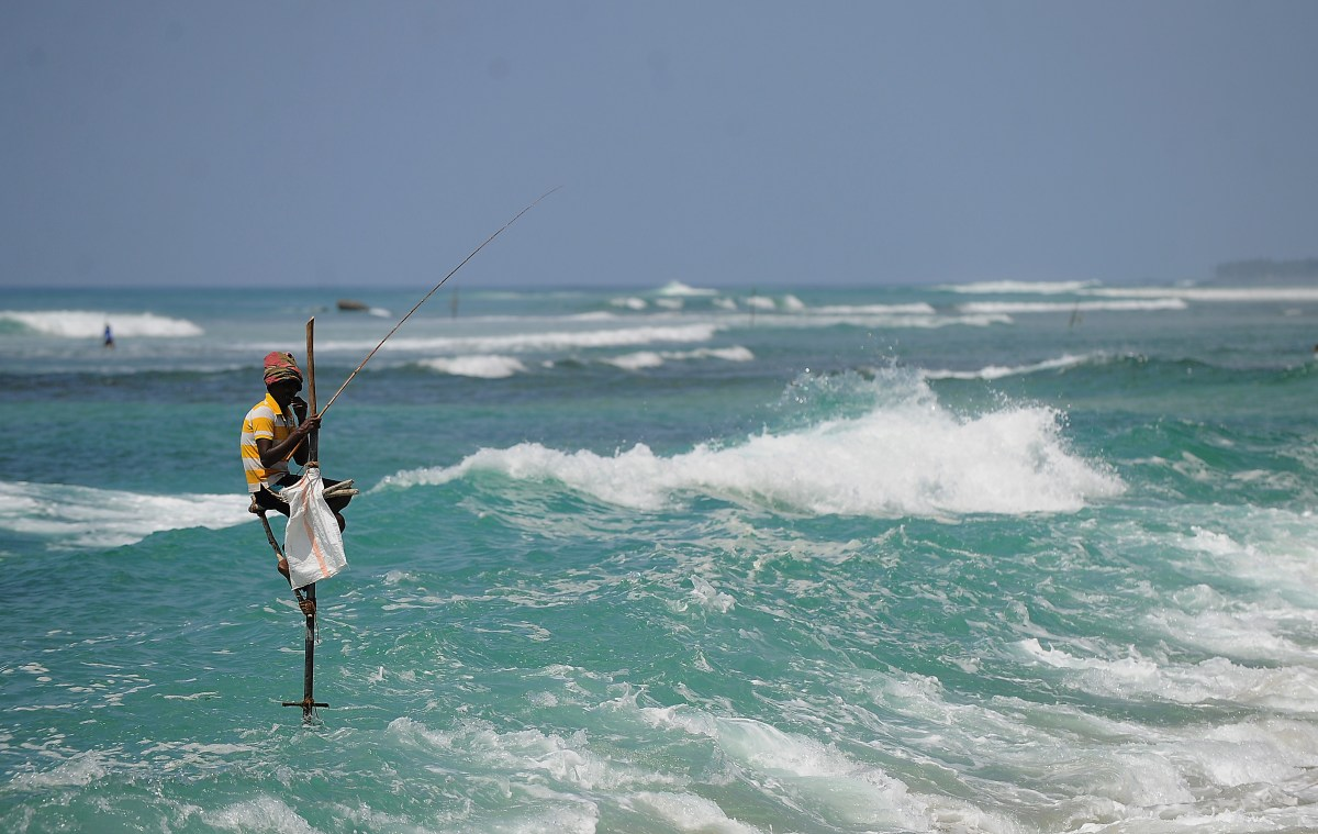 A Sri Lankan stilt fisherman works on his pole in the southern town of Galle.