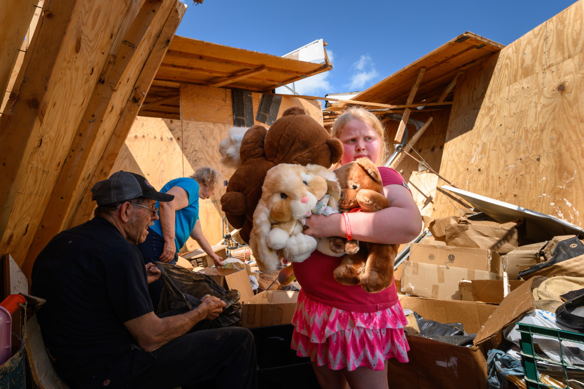 Nine-year-old Keeley Frank holds stuffed animals her grandparents Al and Barb Scheidegger (at left) salvaged from their storage unit on May 23rd, 2019, in Jefferson City, Missouri. It was among many units destroyed by a tornado there on Thursday.