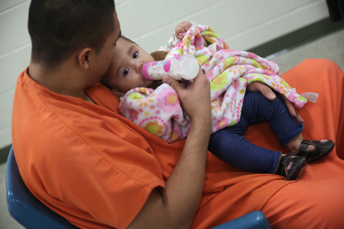 An immigrant feeds his daughter during a family visitation at the Adelanto Detention Facility, in San Bernardino County, California.