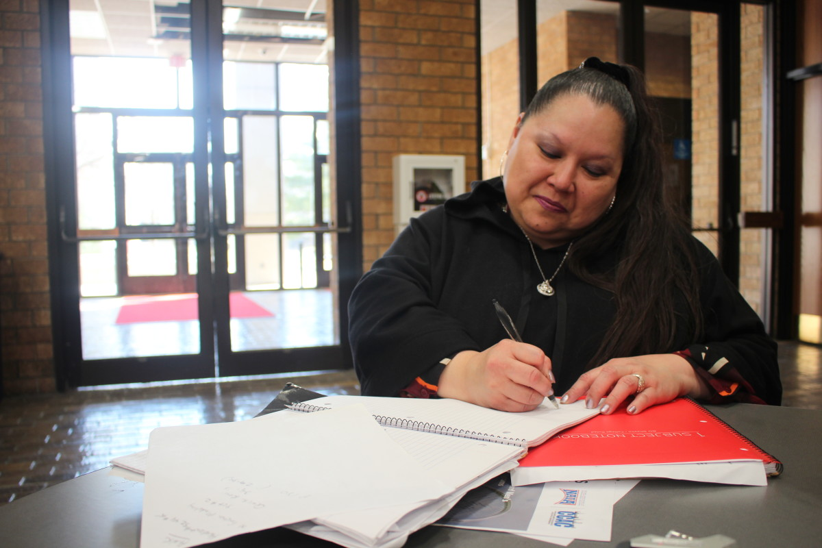 Hsiulien Perez jots down notes in Hawthorn Hall just before heading to an afternoon class.