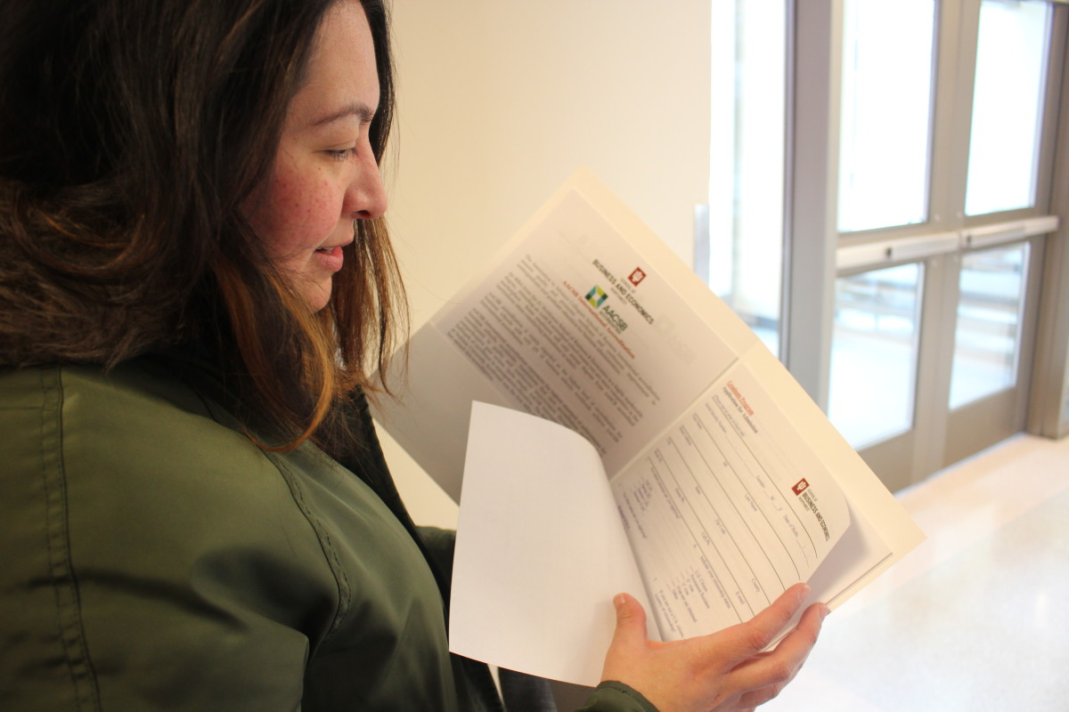 Anel Chavez, a recent graduate of Indiana University–Northwest, picks up an application for the school's business and economics graduate program.
