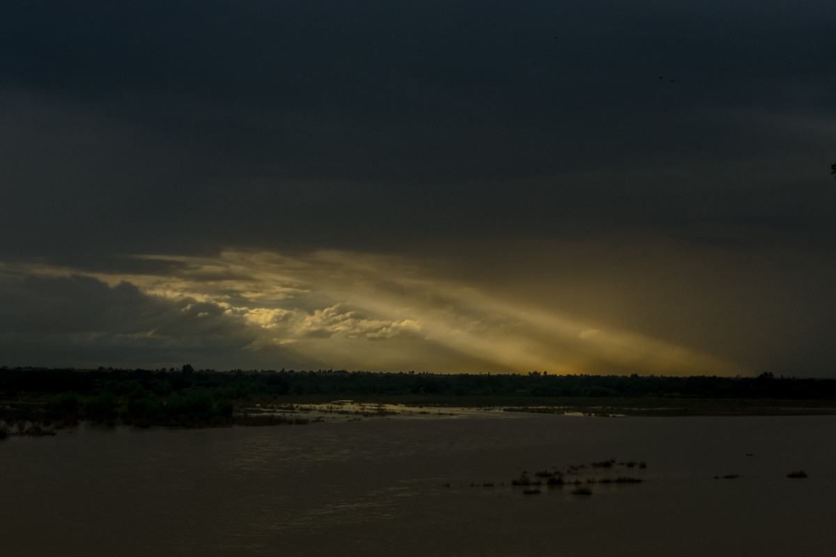 Across the overflowing Helmand River from Lashkar Gah, sunlight breaks through the clouds over Nad Ali in April of 2019.