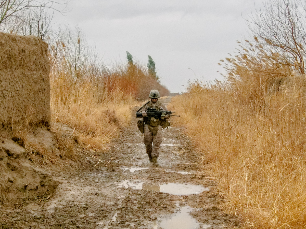 A Marine from the author's squad walks down a muddy goat trail on patrol in Marjah during the spring of 2011.