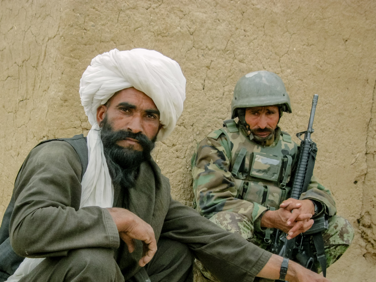 An Afghan National Army solider watches a local man have his photo taken during a patrol in the winter of 2010.