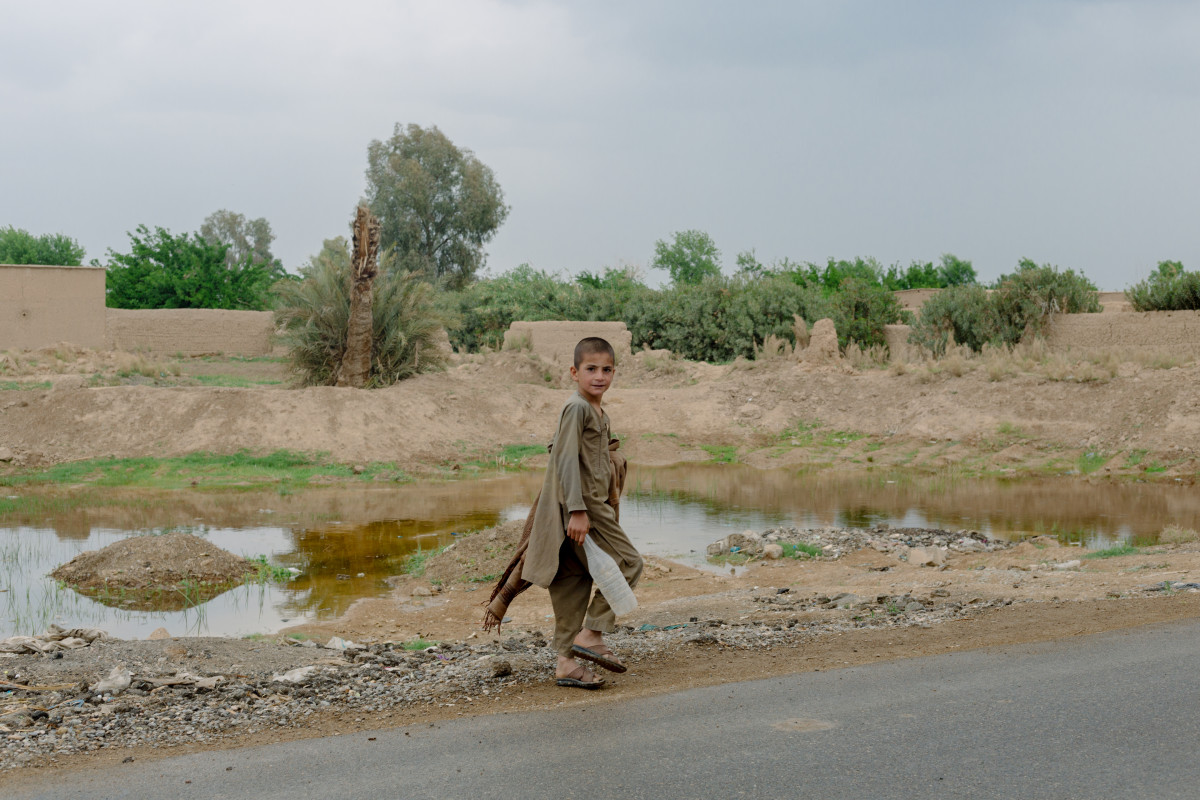 In April of 2019, a boy walks past a small pond formed by a single U.S. bomb dropped during heavy fighting to retake Nad Ali, two years earlier.