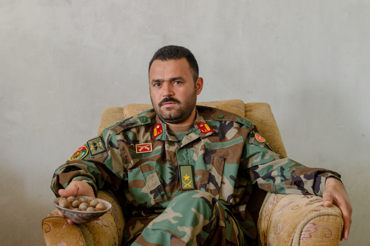 Afghan National Army Major Hedayat Rasouly sits in his office in April of 2019 holding the remains of a shaped charge bomb. The bomb was planted by the Taliban and later defused by explosive ordinance disposal specialists from Rasouly's brigade.